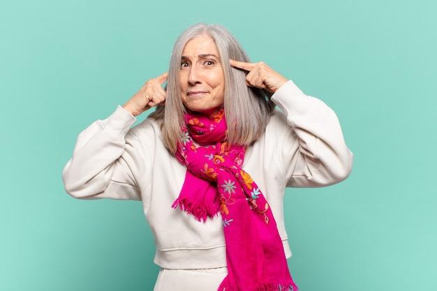 집중하고 생각에 열심히 생각하고 도전이나 문제에 대한 해결책을 상상하는 중년 여성