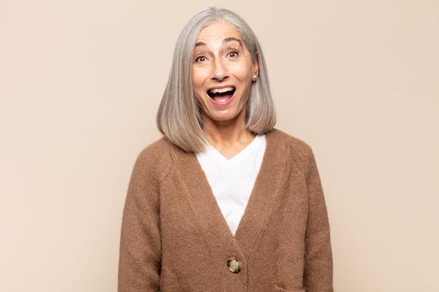 Женщина средних лет выглядит счастливой и приятно удивленной, взволнованной, с очарованным и шокированным выражением лица