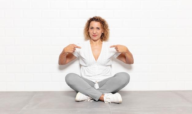 誇らしげで前向きでカジュアルな中年女性が両手で胸を指さ