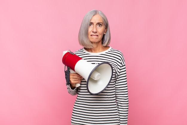 Middle aged woman looking puzzled and confused, biting lip with a nervous gesture, not knowing the answer to the problem with a megaphone
