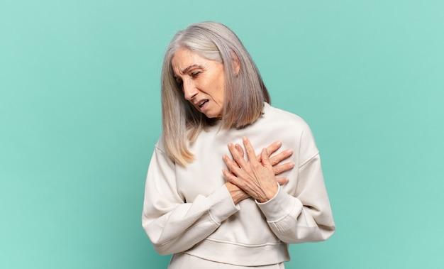 Женщина средних лет выглядит грустной, обиженной и убитой горем, держит обе руки близко к сердцу, плачет и чувствует себя подавленной Premium Фотографии