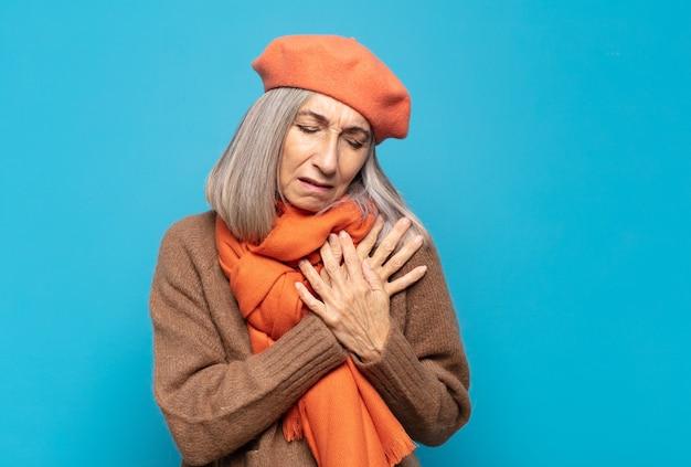 Женщина средних лет выглядит грустной, обиженной и убитой горем, держит обе руки близко к сердцу, плачет и чувствует себя подавленной