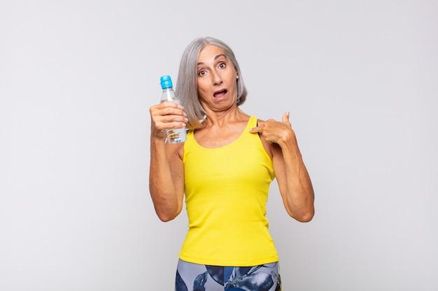 Женщина средних лет выглядит шокированной и удивленной с широко открытым ртом, указывая на себя