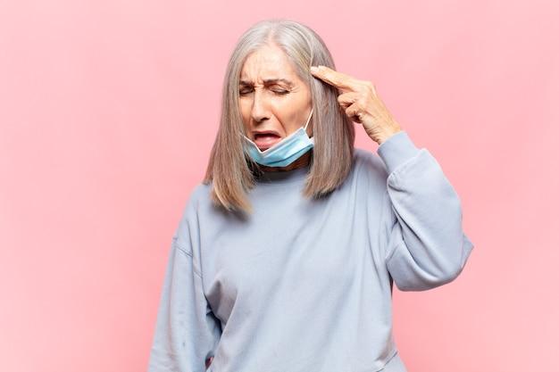 Женщина средних лет выглядит несчастной и подчеркнутой, жест самоубийства делает знак пистолета рукой, указывая на голову