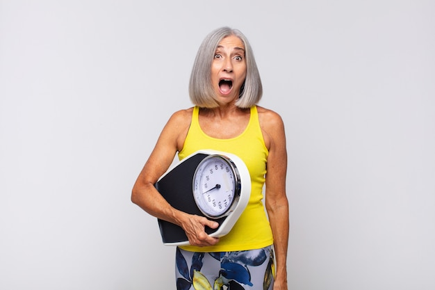 Middle aged woman looking very shocked or surprised, staring with open mouth saying wow