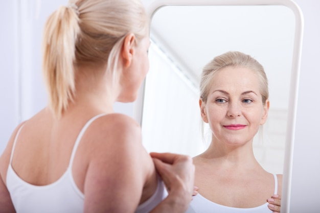 Middle aged woman looking at wrinkles in mirror. selective focus
