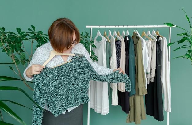 中年女性は買い物をし、棚の近くの新しいドレスを服で見ます。