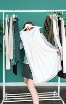 Женщина средних лет делает покупки и смотрит на новое платье возле полки с одеждой.