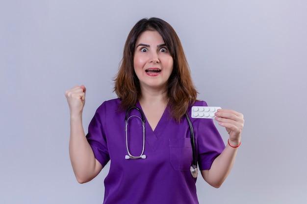 中年女性看護師の医療制服を着て、幸せなカメラ目線の丸薬とブリスターを保持している聴診器で、whiの上に立って勝利勝者の概念の後に拳を上げて終了