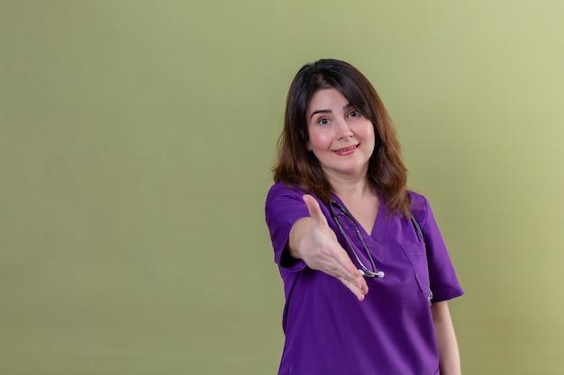Среднего возраста женщина медсестра носить форму и с помощью стетоскопа, улыбаясь, дружественных предлагая руку, делая жест приветствия над изолированной зеленой стене