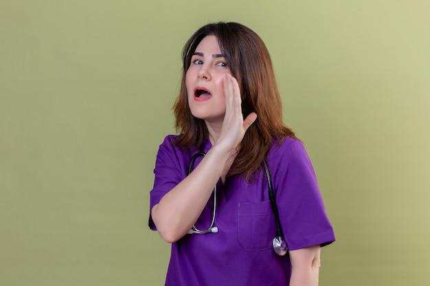 Uniforme d'uso della donna dell'infermiera di mezza età e con lo stetoscopio con una bocca vicina della mano che dice una parete verde isolata sopra segreta