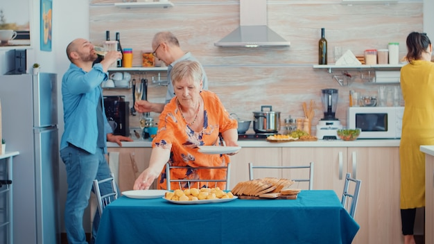 Middle aged woman and older senior have fun working together setting the dinner table in kitchen, while men talking in background and drinking a glass of white wine during a relaxing family day.