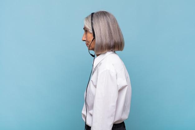 Женщина средних лет на виде профиля, желающая скопировать пространство впереди, думает, воображает или мечтает