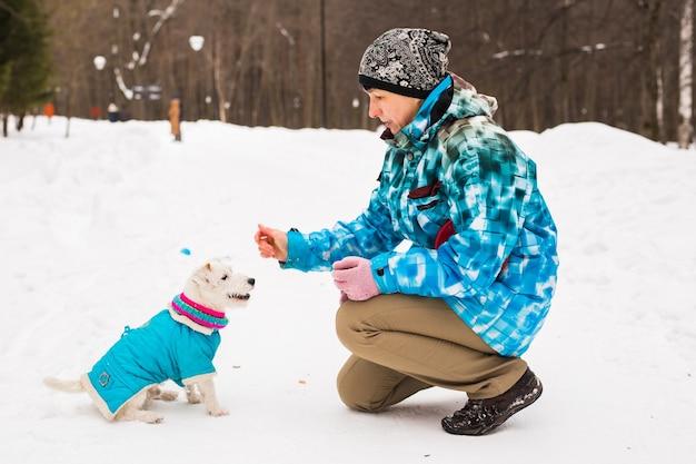 かわいい犬と屋外の中年女性-冬のジャックラッセルテリア