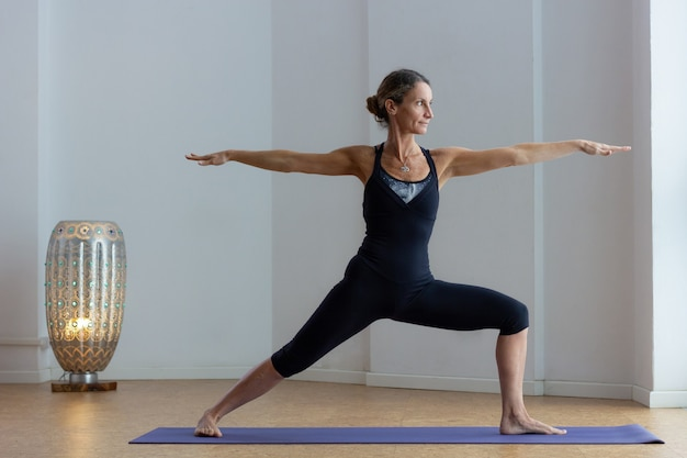 Middle aged woman performing virabhadrasana indoors slim yogi in black outfit doing warrior pose