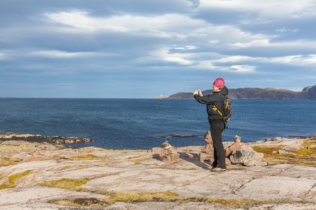 A middle-aged woman photographs the barents sea., travel concept