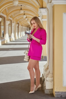 Middle aged woman in pink suit with smartphone in hands is standing in  arched trade gallery.