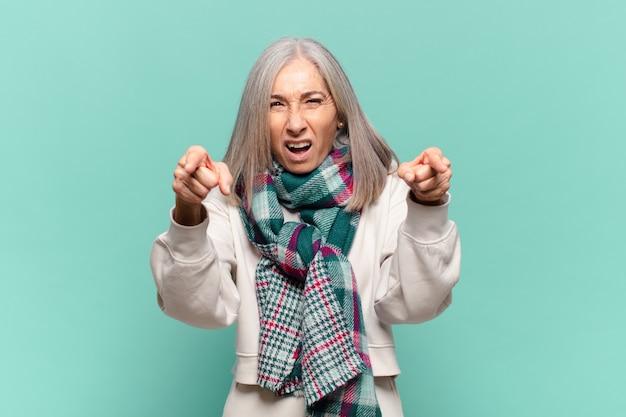 指と怒りの表情でカメラを前に向けて、義務を果たすように言っている中年女性