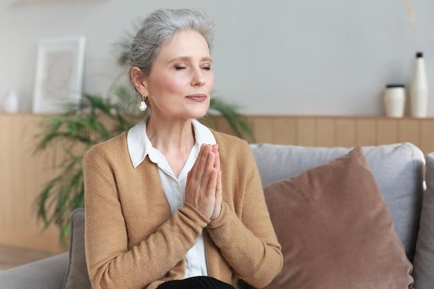 Женщина средних лет молится с закрытыми глазами, смотрит вверх, надеется на лучшее, просит прощения.