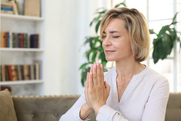 Женщина средних лет молится, глаза открыты, смотрит вверх, надеется на лучшее, просит прощения.
