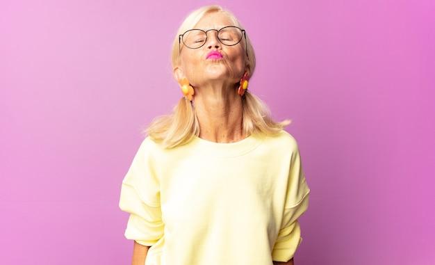 キュートで楽しく、幸せで、可愛らしい表情で唇を押してキスをする中年女性