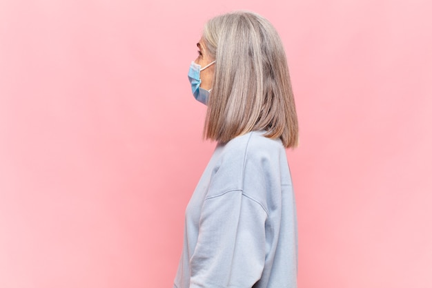 Middle aged woman on profile view looking to copy space ahead, thinking, imagining or daydreaming