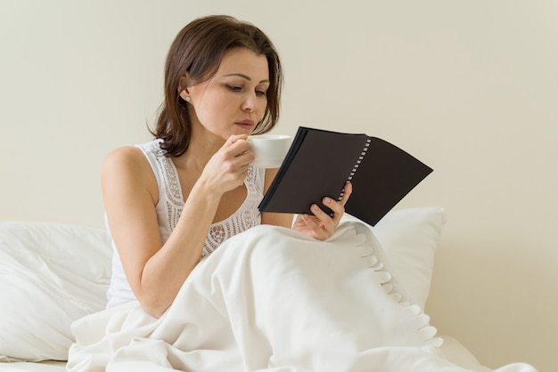Middle-aged woman reading notebook holding cup