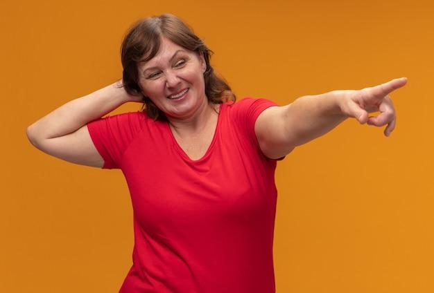 Donna di mezza età in maglietta rossa che osserva da parte con la mano sulla sua testa che punta il dito indice witn a qualcosa che sorride in piedi sopra la parete arancione