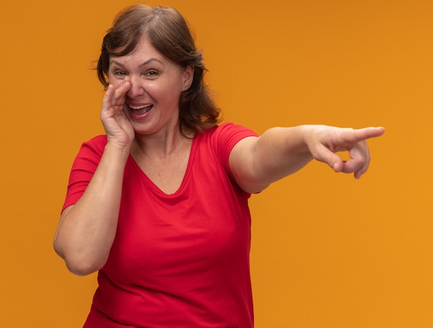 Middle aged woman in red t-shirt  smiling telling a secret with hand near mouth pointing with index finger at something standing over orange wall