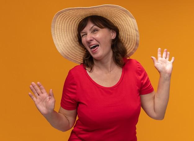 Donna di mezza età in maglietta rossa e cappello estivo sorridente felice e allegro con le braccia alzate in piedi sopra il muro arancione