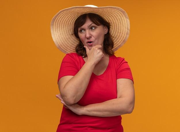 Donna di mezza età in maglietta rossa e cappello estivo che guarda da parte con espressione pensierosa pensando in piedi sopra la parete arancione