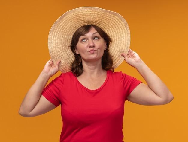 Donna di mezza età in maglietta rossa e cappello estivo che osserva in su in piedi felice e positivo sopra il muro arancione