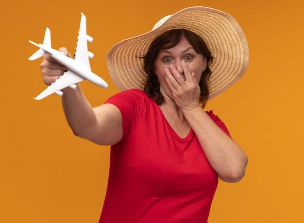 Donna di mezza età in maglietta rossa e cappello estivo che mostra aeroplano giocattolo sorpreso che copre la bocca con la mano in piedi sul muro arancione