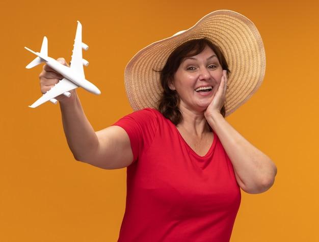 Donna di mezza età in maglietta rossa e cappello estivo che mostra aeroplano giocattolo felice e allegro sorridente in piedi sopra la parete arancione