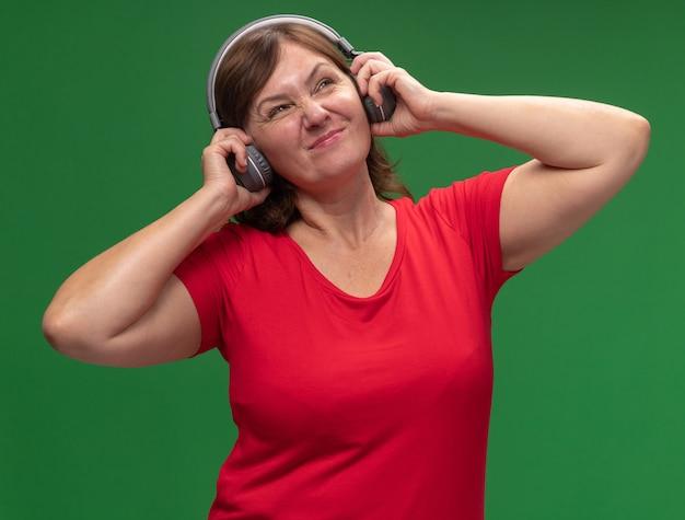 Donna di mezza età in maglietta rossa con le cuffie che ascolta la musica dispiaciuta in piedi sopra la parete verde