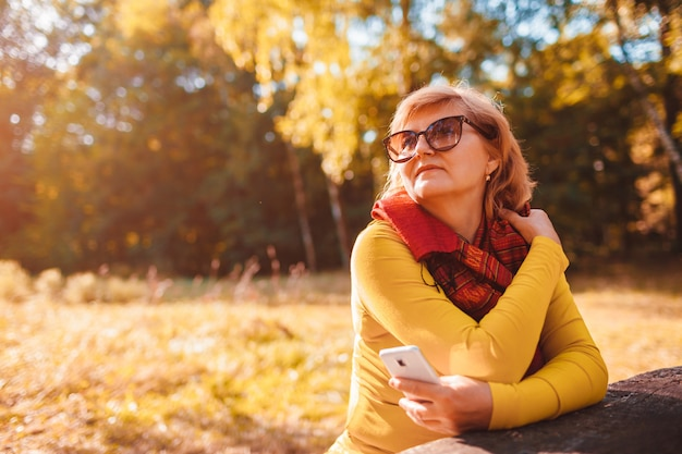 Middle aged woman relaxing using phone outdoors