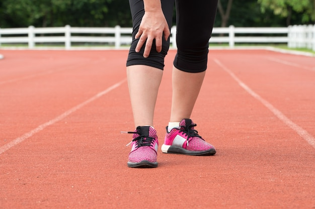 Middle aged woman runner knee pain during training outdoors.