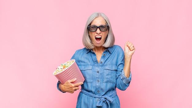Женщина средних лет агрессивно кричит с гневным выражением лица или со сжатыми кулаками, празднуя концепцию фильма об успехе