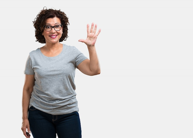 Middle aged woman showing number five, symbol of counting, concept of mathematics