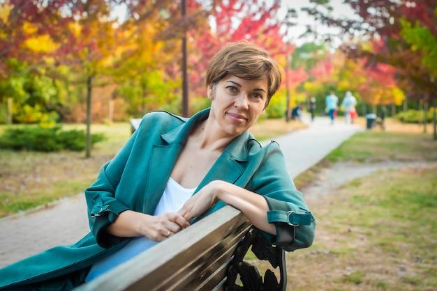 중년 여성은 가을 공원 벤치에 앉아 있다. 오렌지 잎. 노인에 대한 개념