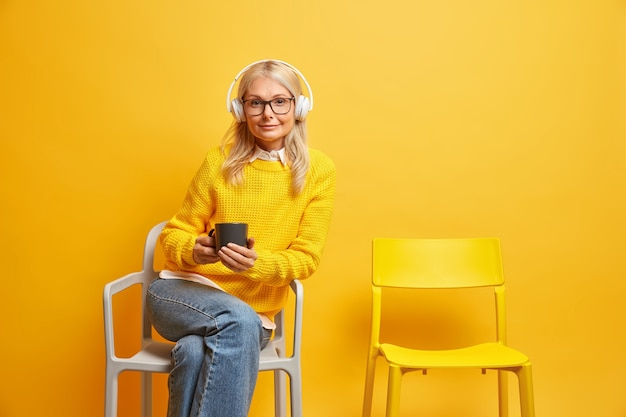 Женщина средних лет сидит на удобном стуле, носит прозрачные очки, держит кружку кофе, слушает музыку в наушниках