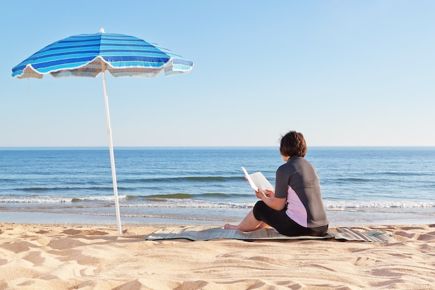 Middle-aged woman sitting on the beach reading a book. under a beach umbrella.