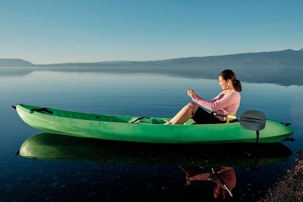 강가의 카약에 앉아있는 중년 여성이 풍경 사진과 동영상을 찍고 있습니다. 그녀의 취미를 즐기고 있습니다.