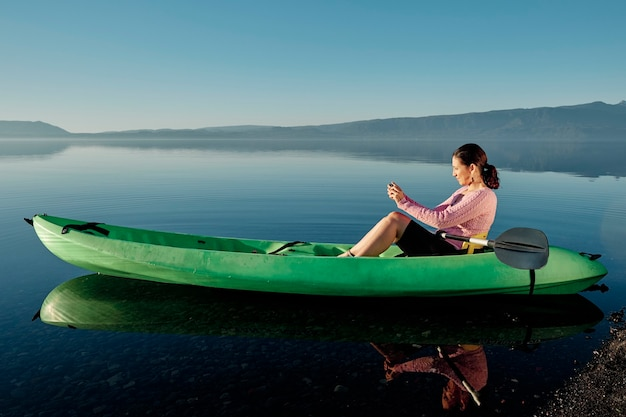 Middle-aged woman sitting in a kayak by a river taking pictures and videos of the landscape. enjoying her hobbies.