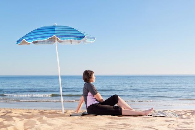 Среднего возраста женщина сидит на пляже беззаботно и расслабляющий. под пляжным зонтом.