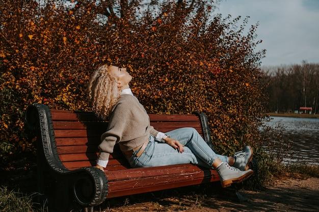 Женщина средних лет сидит на скамейке в осеннем городском парке