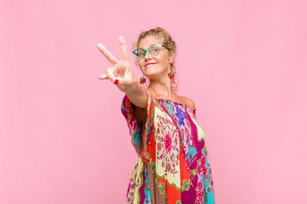 Женщина средних лет улыбается и выглядит счастливой, беззаботной и позитивной, жестикулирует победу или мир одной рукой
