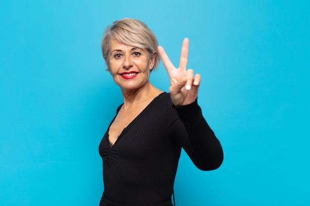 Женщина средних лет улыбается и выглядит счастливой, беззаботной и позитивной, жестикулируя победу или мир одной рукой