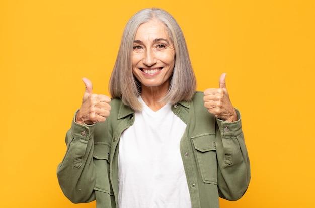 Женщина средних лет широко улыбается, выглядит счастливой, позитивной, уверенной и успешной, с поднятыми вверх большими пальцами