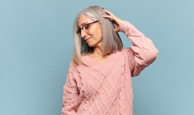 Женщина средних лет весело и небрежно улыбается, взявшись за голову с позитивным, счастливым и уверенным взглядом